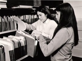 Photo of two women in file room.