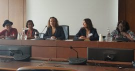 Photo of five people sitting at the front of a room presenting.
