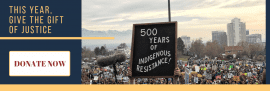 photo of Native woman at protest with sign: 500 years of indignous resistance