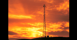 Photo of cellular tower silhoutted by sunset