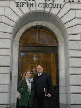 a woman and a man standing in front of courthouse door