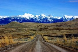 Photo of long dirt road leading to mountains in Montana