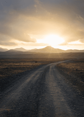 Photo of dirt road leading to sunlit mountains in distance