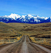 A dirt road leads to distant Montana mountains
