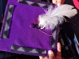 Photo of eagle feather attached to beaded graduation cap