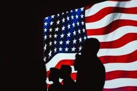 Sihouettes of people on US flag. Credit: Brett Sayles